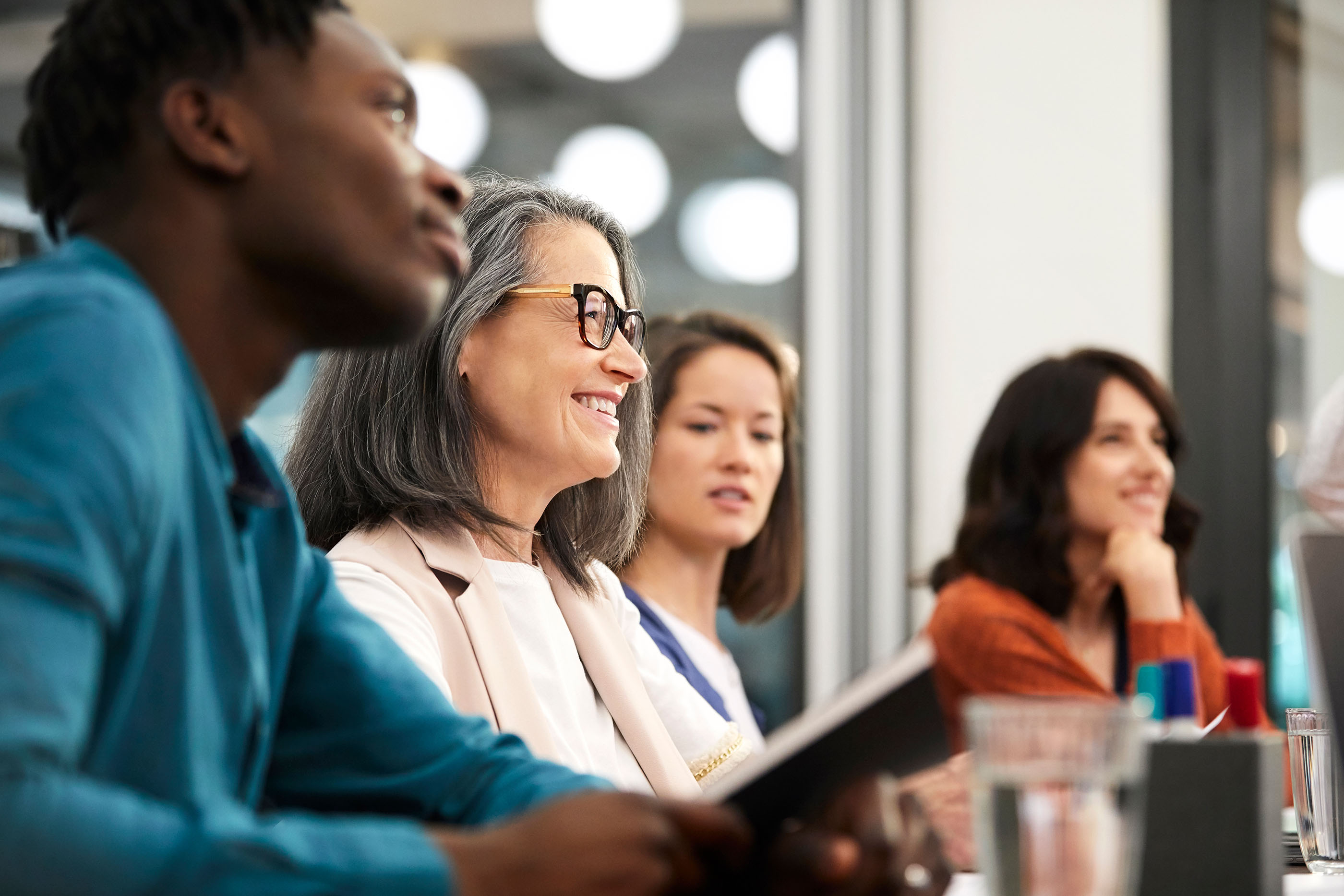 Vier Personen sitzen an einem Konferenztisch