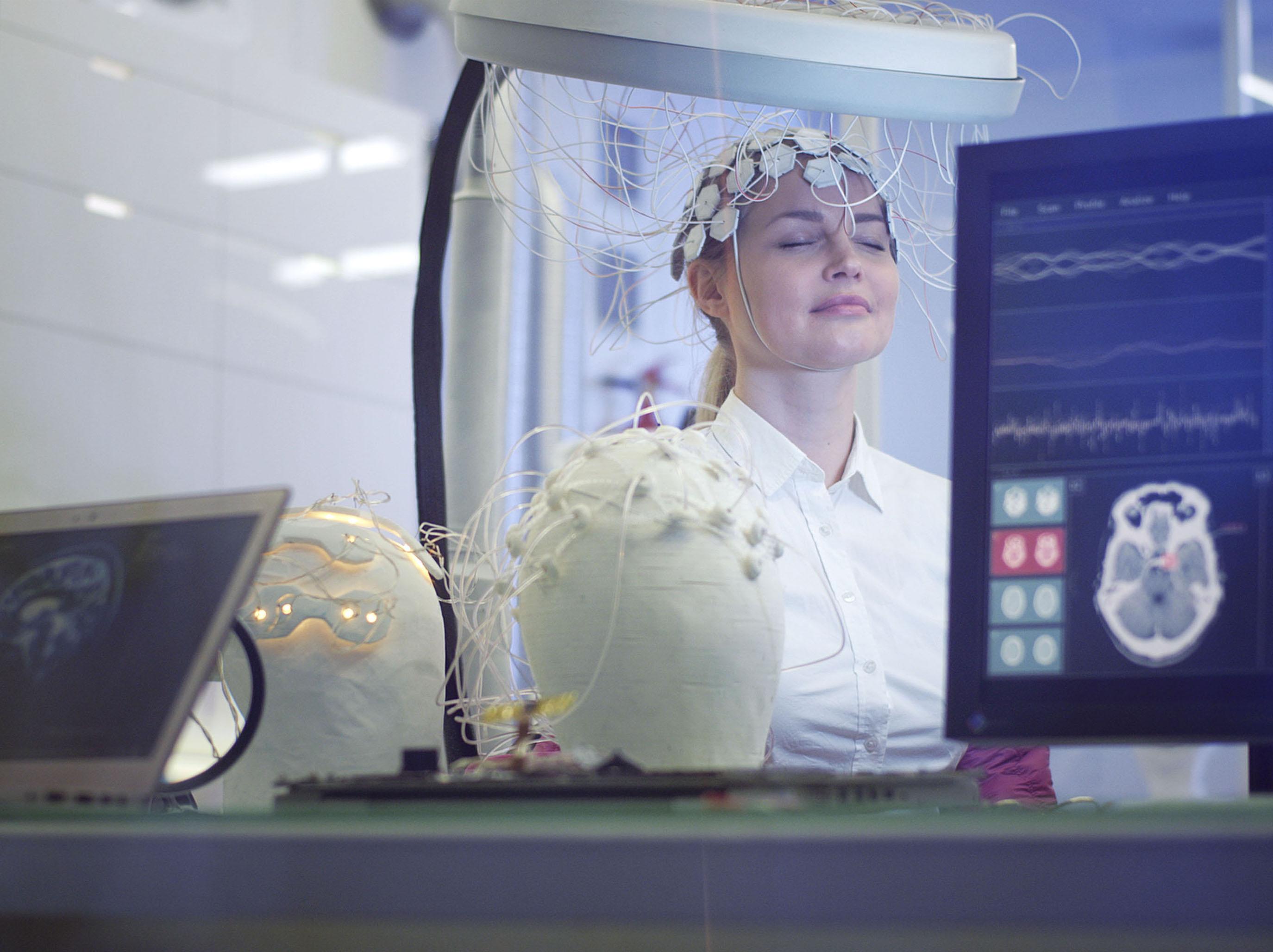 Frau trainiert Gehirn mittels Neurofeedback und hat mit Elektroden am Kopf
