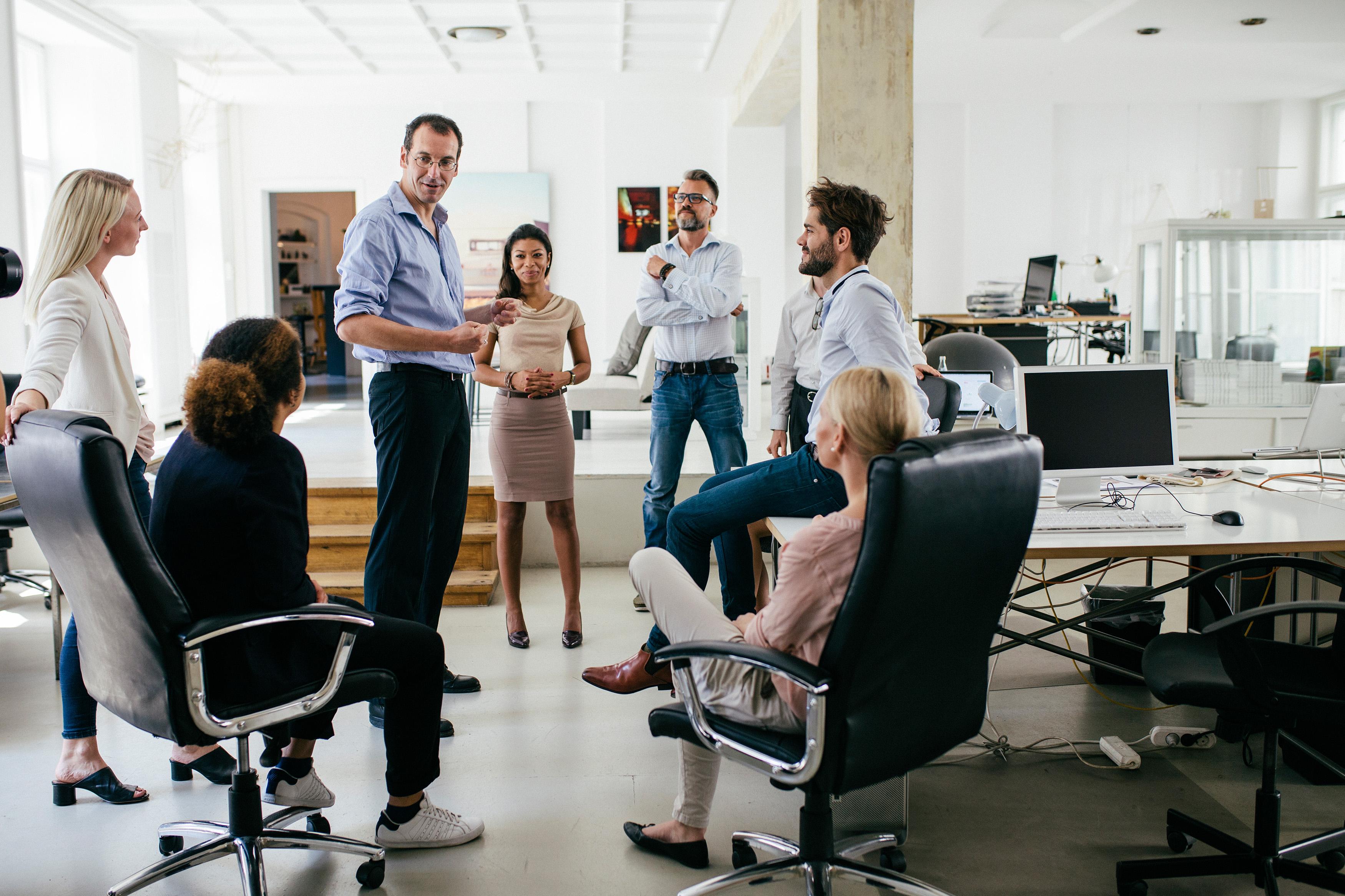 Führungskraft steht inmitten von Mitarbeiterinnen und Mitarbeitern.