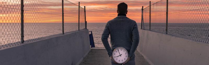 Mann blickt aufs Meer mit einer Uhr in den Händen.