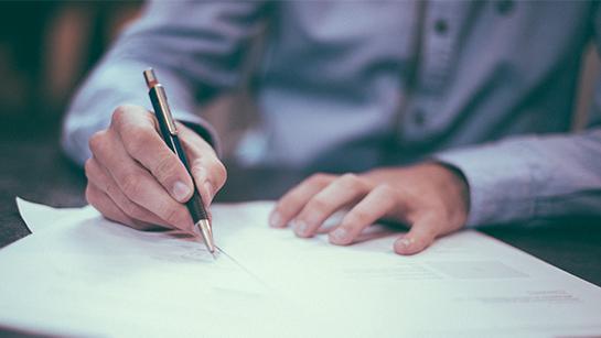 Männerhände, die ein Dokument unterschreiben