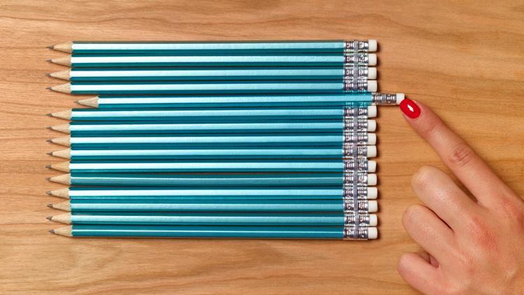 Frau schiebt Bleistifte in eine Reihe