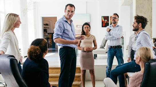Menschen stehen im Büro um Vorgesetzten