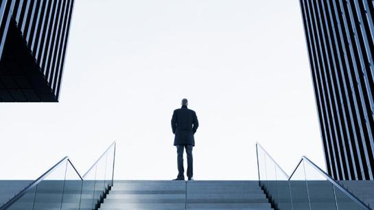 Mann steigt Treppe zwischen zwei Hochhäusern