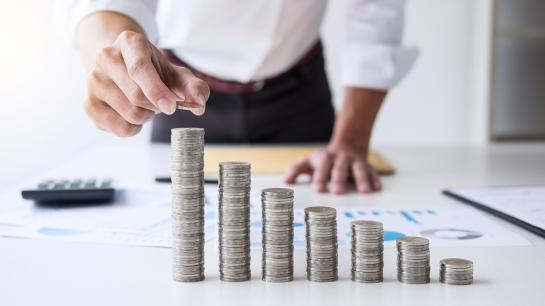 Münzgeld, das in absteigender Höhe auf verschieden hohe Stapel gelegt wird