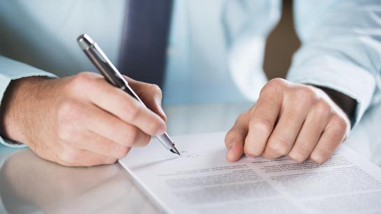 Hände eines Mannes unterzeichnen einen Vertrag