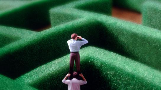 Spielfiguren schauen mit Fernglas über eine Hecke