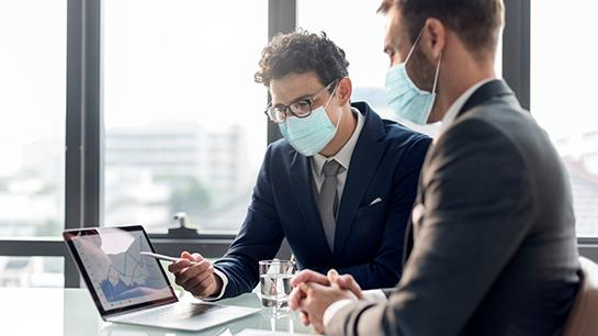 Männer mit Maske an einem Schreibtisch mit einem Macbook